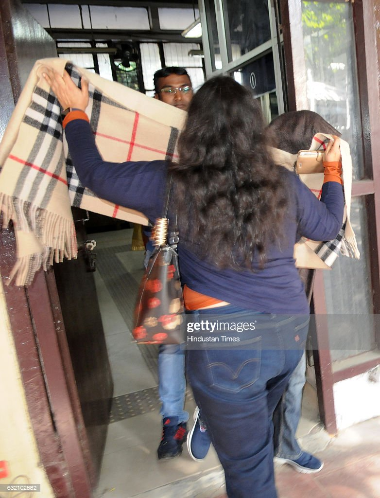 A relative covers the wife of Siddharth Vashisht as she arrives at DC office for her marriage registration on January 19 2017 in Chandigarh India...