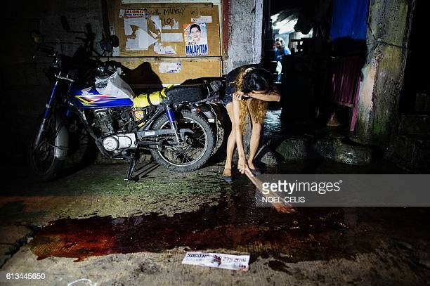 A relative cries as she sweeps the blood of a relative gunned down by unidentified killer in Manila on September 22 2016 Philippine President Rodrigo...