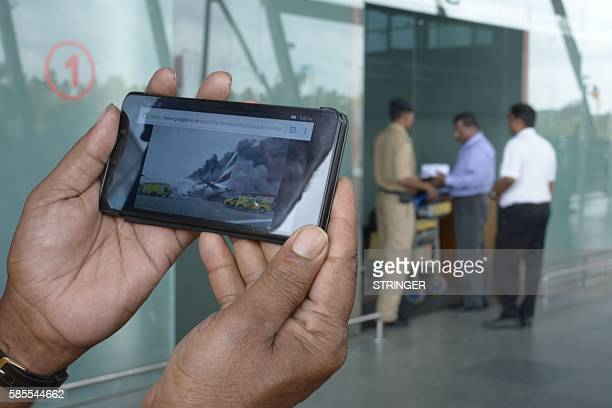 A relative displays a picture of the crashed Emirates aircraft EK521 which flew from Thiruvananthapuram to Dubai on his mobile phone at the terminal...
