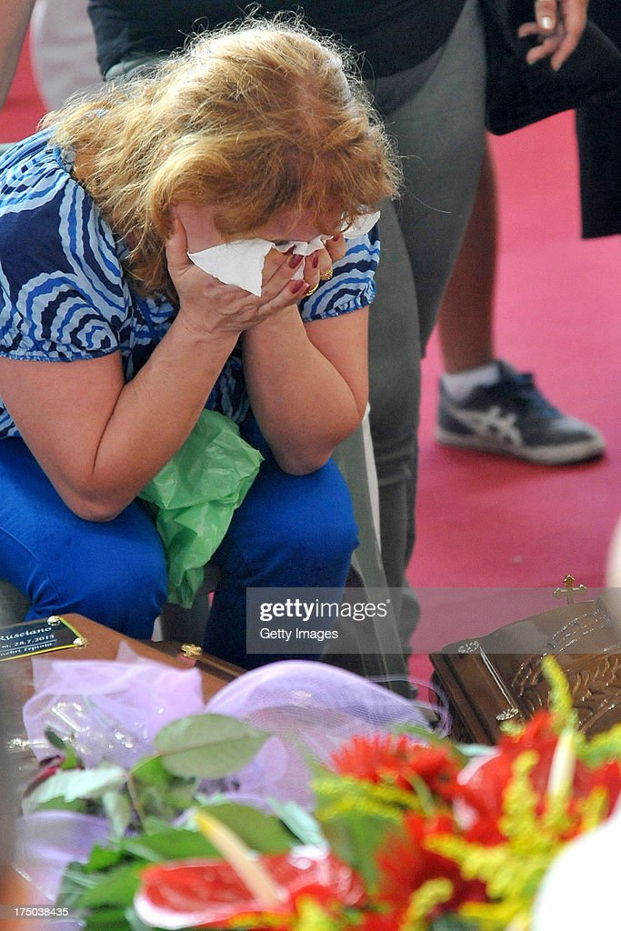 A relative grieves near to the coffins of the victims of the Monteforte Irpino coach crash during the funeral held at a local indoor sports arena on July 30, 2013 in Pozzuoli, Italy. In the second major European transport disaster in a week, 38 people were killed when a coach bus fell from a viaduct near Monteforte Irpino, Italy on July 28.