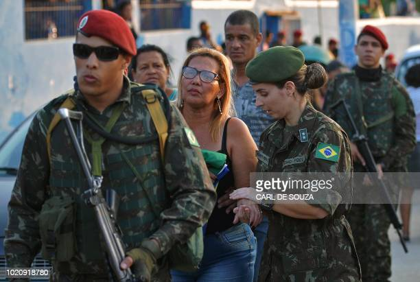 A relative holds a folded Brazilian flag as she is escorted by soldiers after the funeral of soldier Joao Viktor da Silva killed during a militaryled...