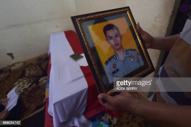 Relative holds a photo of police officer Imam Gilang Adinata who was killed late on May 24 in a suicide bombing, next to his coffin in Jakarta on May...