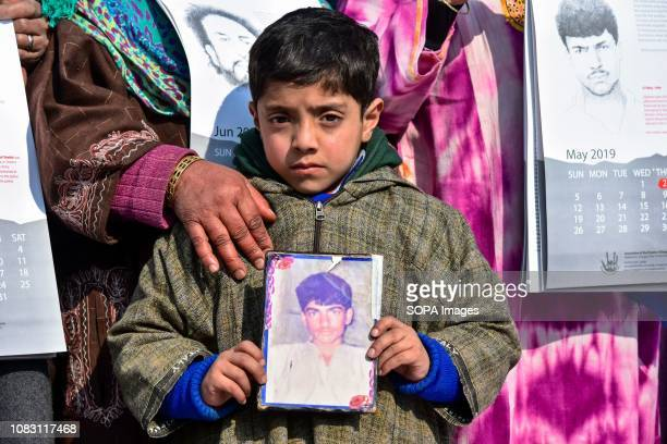 A relative holds a photograph of a disappeared person during a calendar release in Srinagar Indian administered Kashmir Since January 2016 the...
