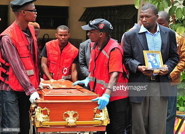 A relative holds a potrait of his relative as he watches her coffin being rolled out by Kenya Red Cross personnel at Chiromo funeral parlour in...
