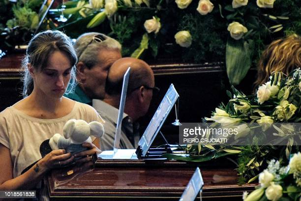 TOPSHOT A relative holds a teddy bear as she mourns near the coffin of a victim of the collapsed Morandi highway bridge prior to the start of the...