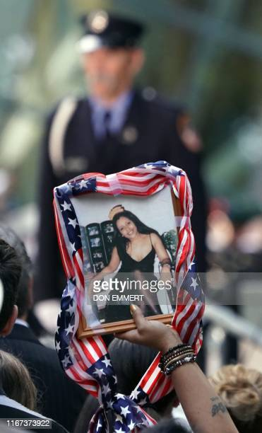 A relative holds the portrait of a victim during the September 11 Commemoration Ceremony at the 9/11 Memorial at the World Trade Center on September...