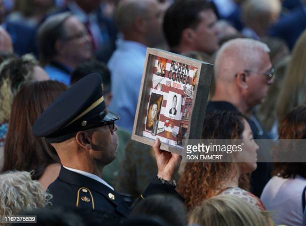 TOPSHOT A relative holds the portrait of a victim during the September 11 Commemoration Ceremony at the 9/11 Memorial at the World Trade Center on...