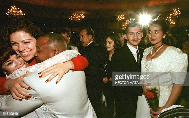 WITH EEUUAMOR BY CLAUDIA RAHOLA A relative hugs a newly married couple after the wedding ceremony at the Hollywood Paladium on Saint Valentine's Day...