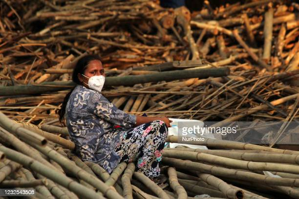 Relative mourns as she sits next to the burning funeral pyres during a mass cremation of victims, who died due to the coronavirus disease, at a...