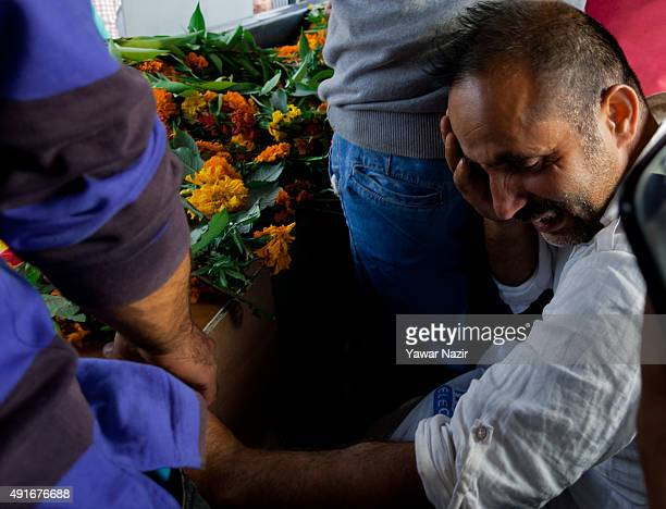 A relative mourns next to the coffin containing the body of a killed Indian police officer after wreath laying ceremony on October 7 2015 in Srinagar...
