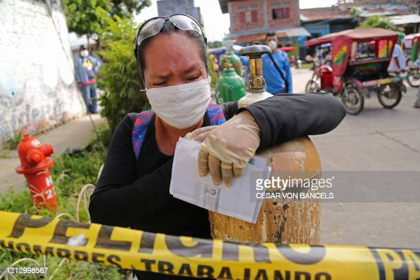 Relative of a COVID-19 patient queues to recharge oxygen tanks for their loved ones at the regional hospital in Iquitos, the largest city in the...