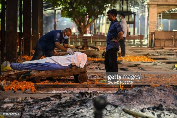Relative of a Covid-19 victim pays his respect before a cremation at Nigambodh Ghat Crematorium on the banks of the Yamuna river in New Delhi in the...