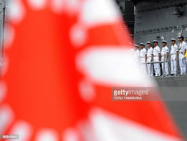 A relative of a crew member aboard Japan's Maritime SelfDefence Force destroyer Harusame waves a navy flag as it embarks on an antipiracy mission off...