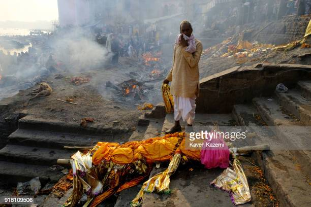 A relative of a deceased man ready for cremation stands next to his body on the stairways of Manikarnika Ghat where in the background burning pyres...