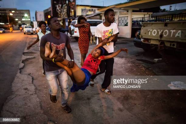 TOPSHOT A relative of a man detained during clashes is carried to the hospital after she fainted on September 1 2016 in Libreville UN...