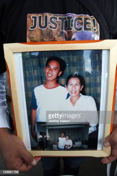 A relative of a massacre victim holds the picture of their loved ones at the where two years prior 58 people 32 of them journalists were killed by...