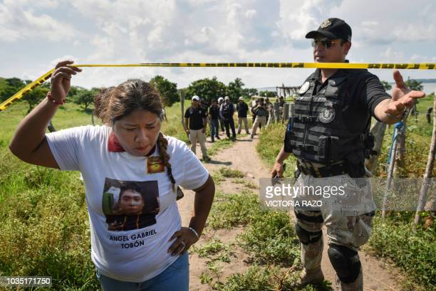 A relative of a missing person enters on September 17 the site where a mass grave was found in El Arbolillo Alvarado municipality in the Mexican...