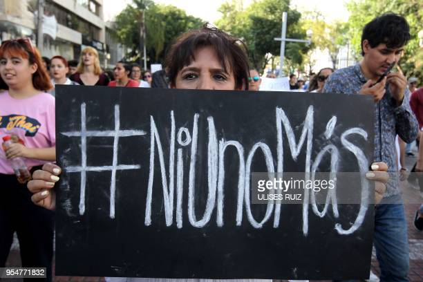 A relative of a missing person holds a placard reading #NotOneMore in Spanish takes part in a massive protest against violence crime and the...