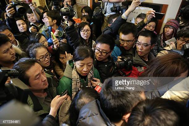 A relative of a passenger onboard Malaysia Airlines flight MH370 is surrounded by the media at Lidu Hotel on March 8 2014 in Beijing China Malaysia...
