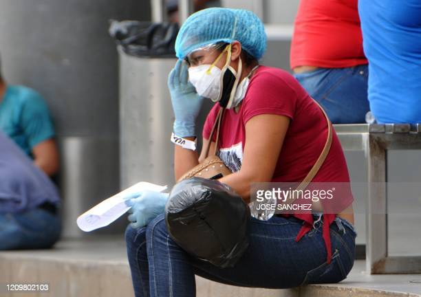 A relative of a patient being treated for COVID19 waits for news of her loved one at the IESS Hospital Los Ceibos in Guayaquil Ecuador on April 13...