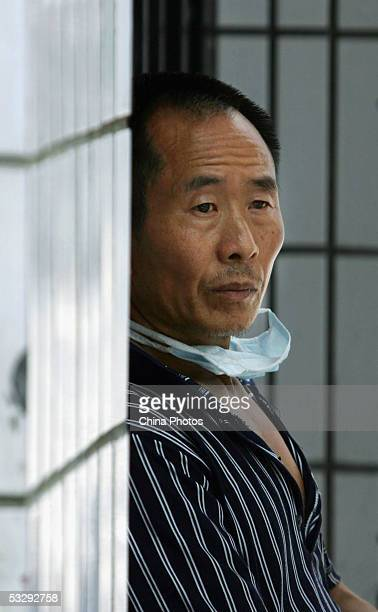 Relative of a patient suffering from a mysterious disease, rests at the infection department of the Ziyang First People's Hospital on July 26, 2005...