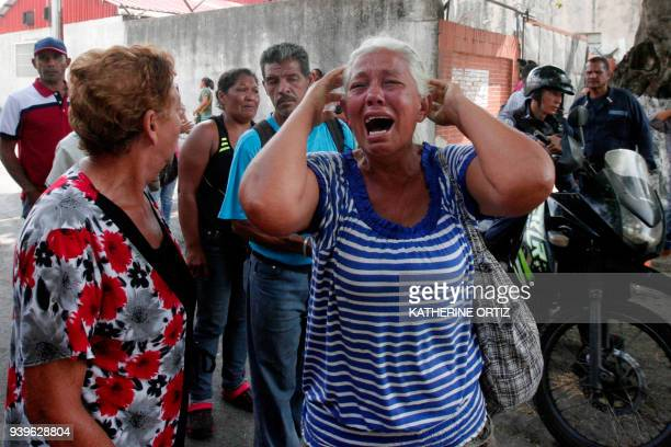 A relative of a prisoner cries in front of a police station in Valencia on March 28 after a fire engulfed police holding cells that resulted in the...