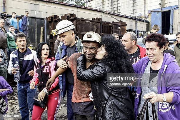 A relative of a rescued miner kisses him as a rescue team member help him to walk outside of the Raspotocje mine in the central town of Zenica during...