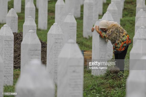 Relative of a Srebrenica Genocide victim mourns by a gravestone at the SrebrenicaPotocari Memorial, ahead of the burial of recently identified...