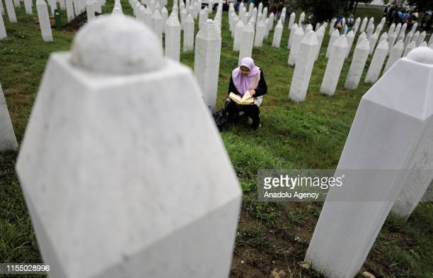 Relative of a Srebrenica Genocide victim recites Holy Quran by a gravestone at the SrebrenicaPotocari Memorial, ahead of the burial of recently...