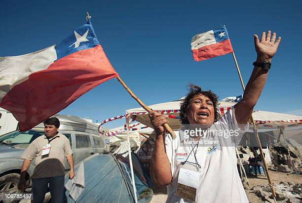 A relative of a trapped miner waves and shouts with a Chilean flag as trucks pass by Campamento Esperanza transporting materials for the rescue of...