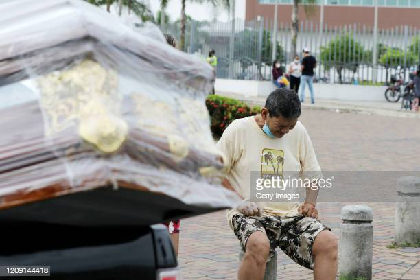 A relative of a victim of coronavirus cries next to the casket that is being transported on a van on April 4 2020 in Guayaquil Ecuador Ecuador's...