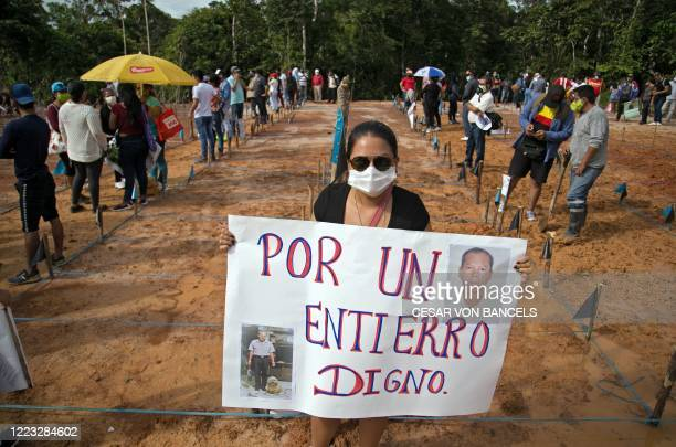 Relative of a victim of COVID-19 holds a sign reading For a dignified burial as she takes part in a protest at the site of a common grave 18...
