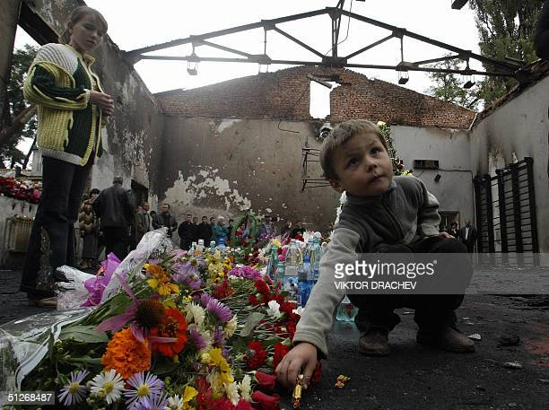 A relative of a victim of the Russian hostage place candie in the gymnasium of the destroyed school in Beslan North Ossetia 07 September 2004 Scores...