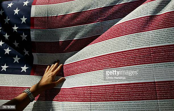 A relative of a victim of the September 11 terrorist attacks looks for a name on a US flag displaying the names of the victims at the World Trade...