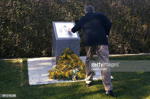 A relative of an Australian victim of Malaysia Airlines flight MH17 touches a memorial that was unveiled outside Parliament House on the first...