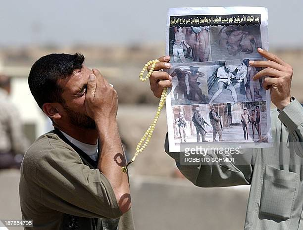 Relative of an Iraqi prisoner being held by US authorities at the Abu Ghraib prison holds his hand to his face 08 May 2004 as another one shows a...