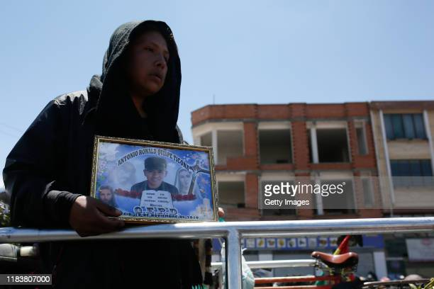A relative of Antonio Ronaldo Quispe Ticona who was killed during clashes with police at the Senkata fuel plant holds his photo during a funeral...