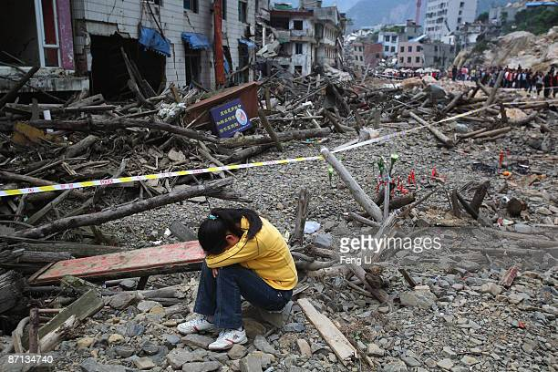 A relative of earthquake victims cries at the ruins of earthquakehit Beichuan county during the one year anniversary of the Wenchuan Earthquake on...