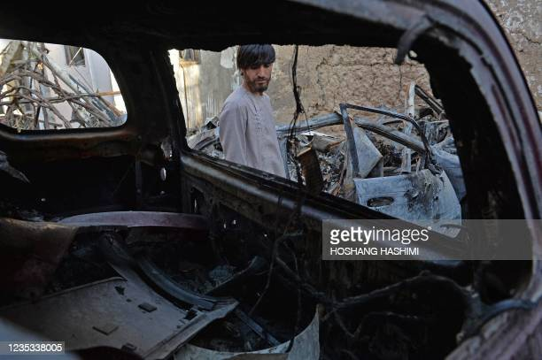 Relative of Ezmarai Ahmadi, is pictured through the wreckage of a vehicle that was damaged in a US drone strike in the Kwaja Burga neighbourhood of...