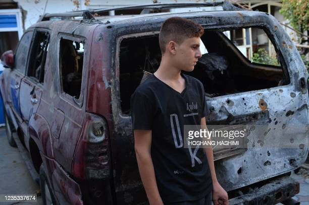 Relative of Ezmarai Ahmadi, stands next to a vehicle that was damaged in a US drone strike in the Kwaja Burga neighbourhood of Kabul on September 18,...