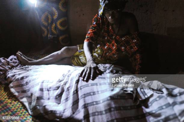 A relative of Mamma Sessay runs her hand across the body of Mamma after she was brought back to the village of Mayogbah the evening of her death from...