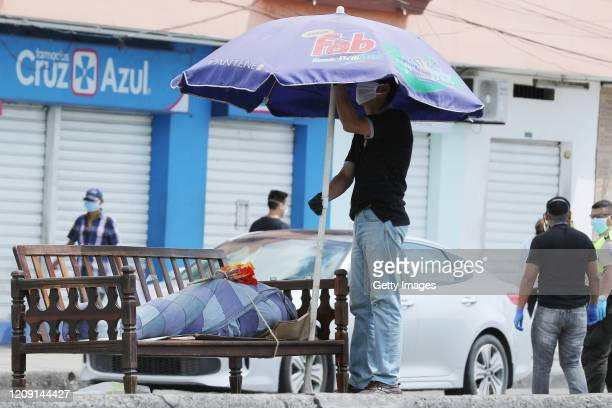 A relative of María Zamora who passed away of a heart attack places an umbrella next to her remains with flowers on a public bench at the south of...
