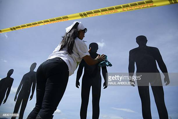 A relative of missing people cleans silhouettes as she attends the first day of search for the bodies disappeared at La Escombrera rubbish dump in...
