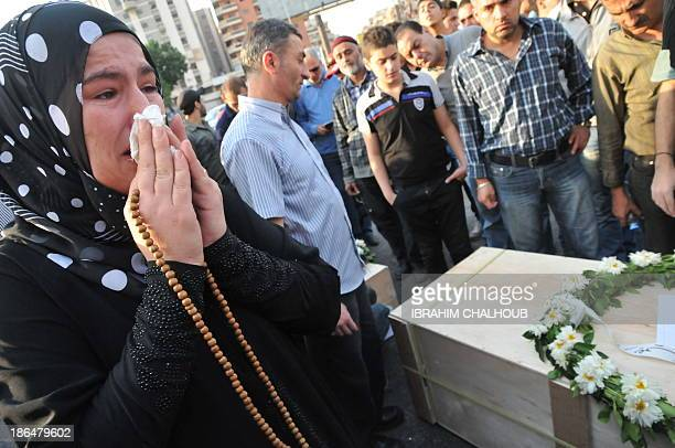 A relative of one of the 34 Lebanese immigrants who drowned in the waters of Indonesia weep as the coffins of victims are handed over to their...