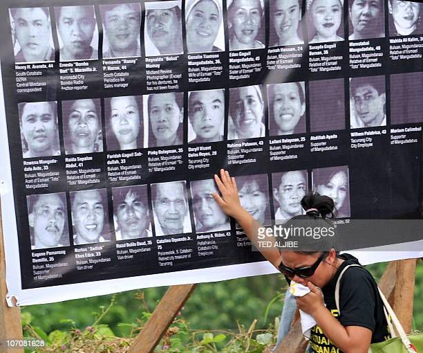 A relative of one of the 57 victims of the November 23 2009 massacre cries as she touches a collage of photos of the victims during a memorial...