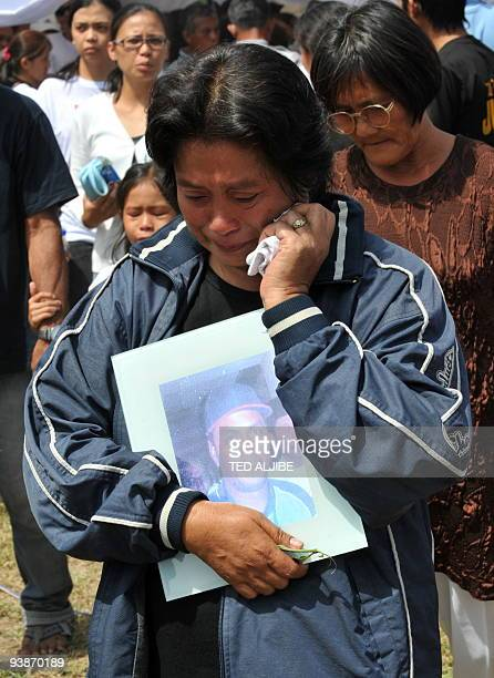 A relative of one of the slain journalists holds a photo during the funeral mass in General Santos City south Cotabato on December 4 2009 Eight of...
