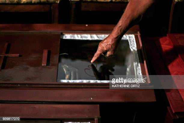 A relative of one of the victims of the prison fire points at the coffin in Valencia on March 29 2018 A total of 68 people died on Wednesday during...