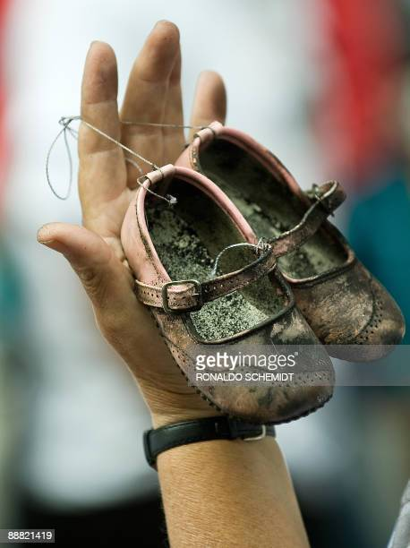 A relative of one of the young victims who died in a fire in a daycare center in Hermosillo Sonora state Mexico last June 5 holds a pair of charred...