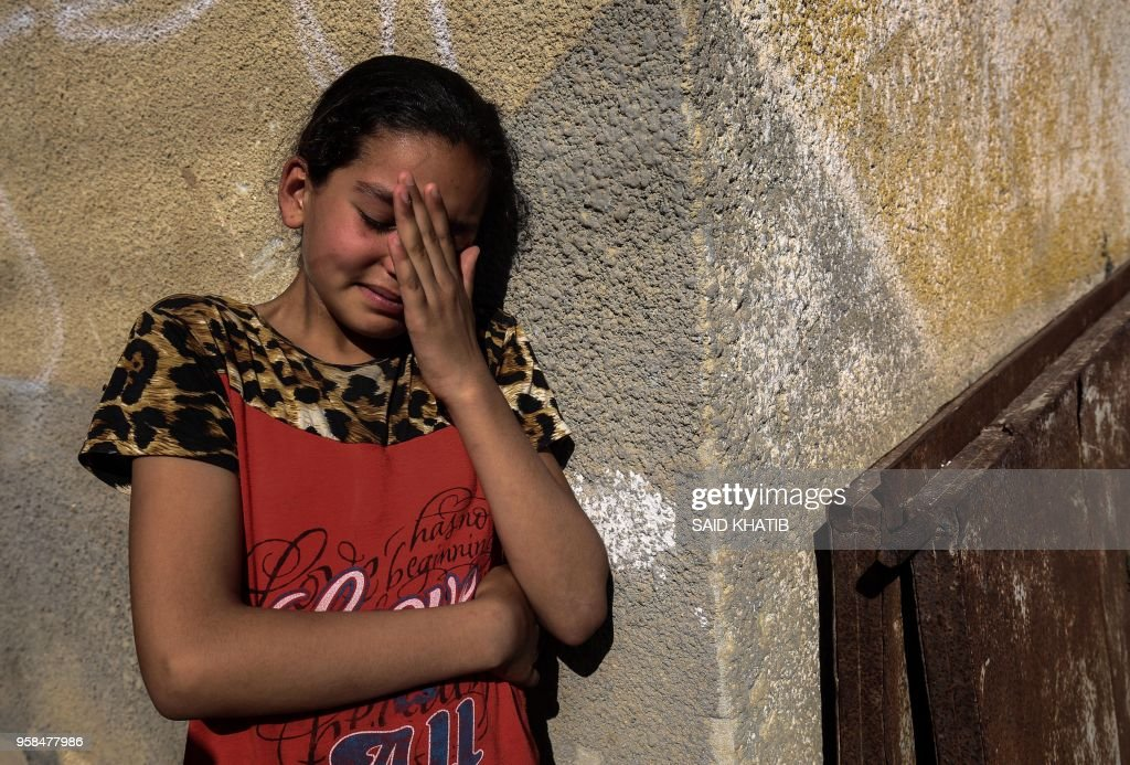 TOPSHOT - A relative of Palestinian Mahmoud Abu Taima, who was killed during a protest at the Israel-Gaza border, mourns during his funeral in Khan Yunis in the southern Gaza Strip on May 14, 2018. - Palestinians followed through with their vow to protest massively along the Gaza border with tens of thousands demonstrating and 52 killed by Israeli fire as clashes erupted over the controversial inauguration of the US embassy in Jerusalem.