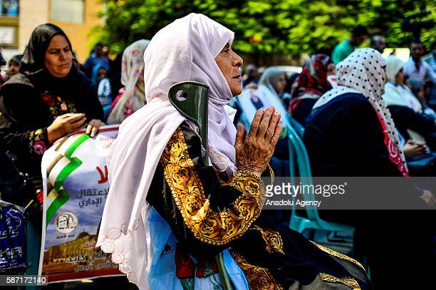A relative of Palestinians imprisoned in Israeli jails holds her hands as if in prayer as she takes part in a demonstration demanding the release of...